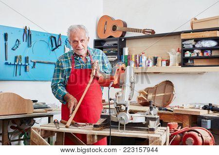 Senior citizen as luthier master working at guitar shop