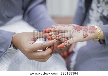 Groom put a wedding ring on bride hand