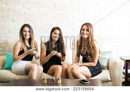 Three young women dressed up and putting on some makeup before going out at night