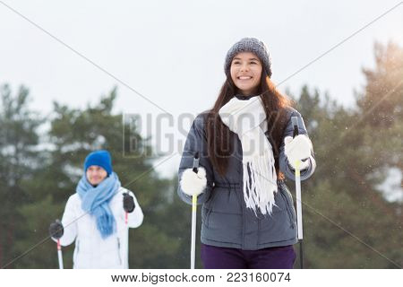Happy young woman in warm winter jacket, white scarf, grey knitted beanie and furry mittens skiing on winter day with her boyfriend