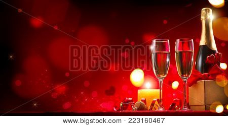 Valentine's Day Romantic Dinner. Date. Table setting with Champagne in two glasses, candles and gift box over holiday red background with hearts. Wedding celebrating. Wide angle format