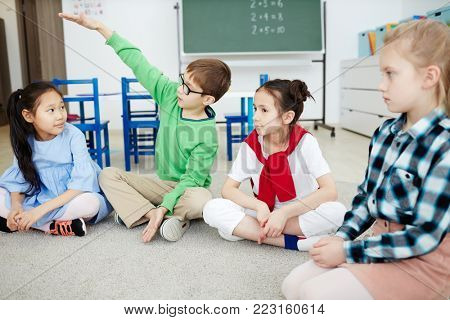 Cute schoolboy explaining something to his classmates while talking on the floor of classroom