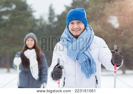 Smiling young man in blue beanie and scarf holding ski sticks and enjoying skiing in snowfall