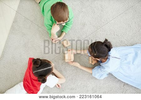 Top view of three friendly schoolkids lying on the floor and building tower from wooden bricks
