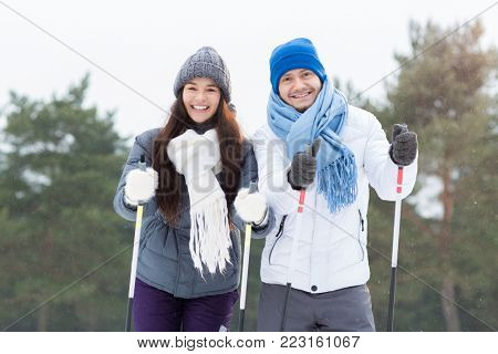 Two young happy skiers looking at camera while enjoying winter day in park