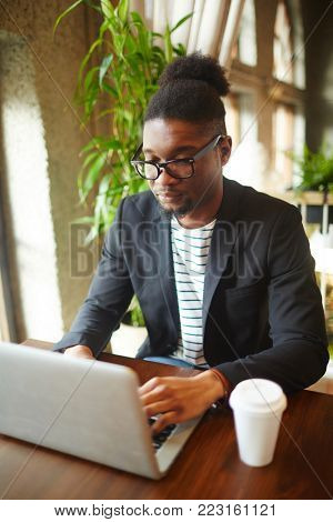 Young African-american manager sitting by table in cafe in front of laptop and networking