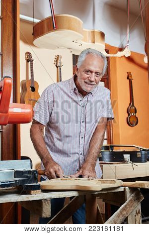 Senior citizen as luthier master makes new guitar at workshop