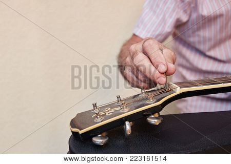 Hand of luthier tuning guitar with wrench with precision