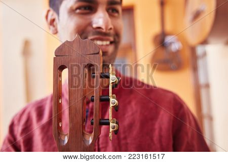 Guitar maker with his new guitar made of wood