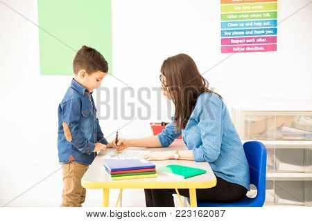 Profile view of a little boy bringing his work to the teacher's desk for grading