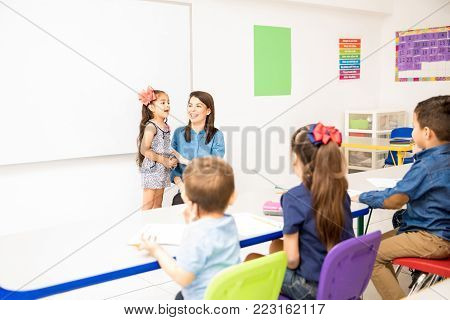 Beautiful little girl participating in class and reciting a poem in a preschool classroom