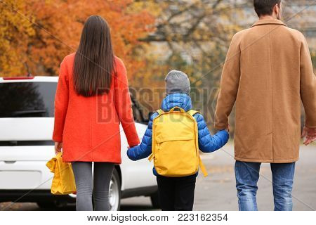 Cute little boy going to school with his parents