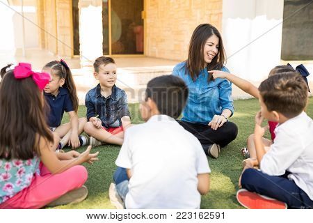 Group of preschool pupils enjoying a class with their teacher outdoors and sitting on the grass