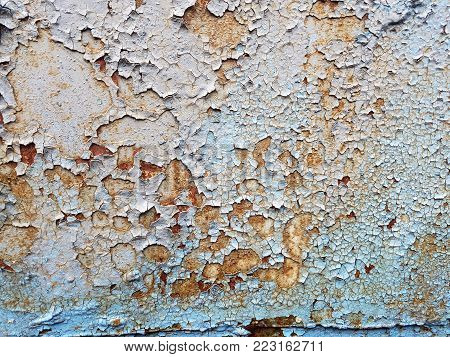 Rough abstract grunge texture of a metal wall with a bluish color with lagging pieces of white paint.