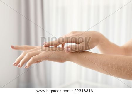Hands of young woman with healthy skin softened by cream with moisturizing effect