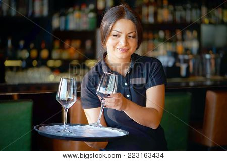The bartender girl brought wine glasses to the client of the hotel bar. Smiling brunette waitress puts the wine glasses on the client's table in the bar. The concept of service.