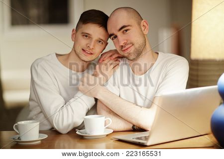 Amorous guys sitting by table with laptop in front and enjoying being together at home