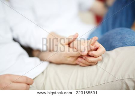 Hands of gay amorous men holding by one another during idyllic moment of life