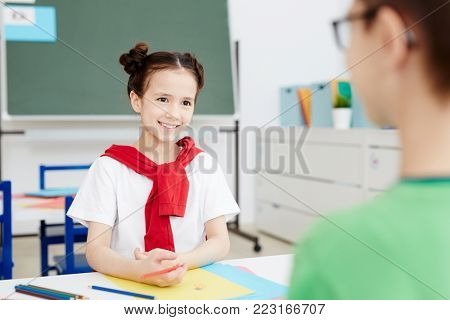 Happy schoolgirl looking at her classmate with smile during talk at lesson of drawing