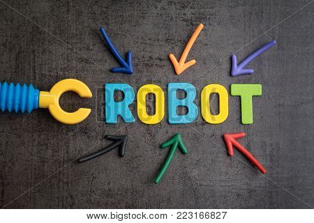 Human jobs replaced by robots concept, multiple arrow pointing to colorful alphabets ROBOT with toy robot arm beside on black cement wall background, robotic and artificial intelligence awareness.