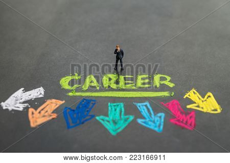 Career path and work opportunities concept by small miniature people businessman standing and thinking on colorful handwriting chalk the word CAREER with multi directional arrow on chalkboard.