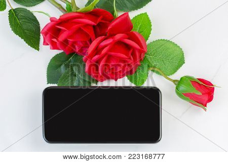 Blank screen of new Smartphone phone next to red roses on marble background, conceptual for giving gift to lover on Valentine's day