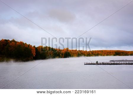 Autumn landscape - the River with a pier in the fall. Beautiful views of autumn landscape - the river, the fog creeps along the river, fishermen catch fish on the pier, around the autumn trees. Around the mist rises from the river.
