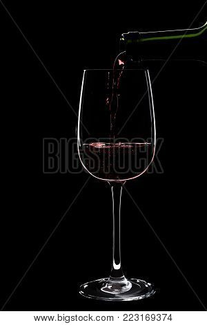 Large glass of red wine is pouring wine from a bottle of red . Filmed in close-up glass, where you pour the wine from the bottle.