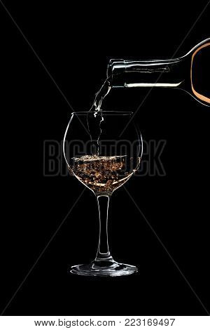 A glass of white wine is pouring wine from a bottle of white. Filmed in close-up glass, where you pour the wine from the bottle.
