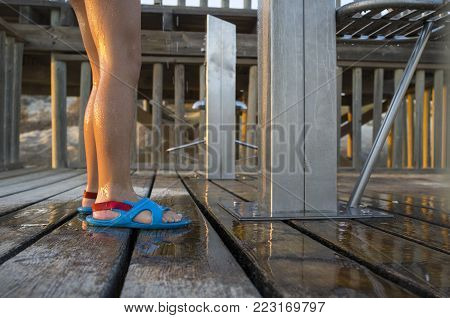 Child removing the sand of the beach on a shower at the entrance to the beach of Islantilla, Huelva, Spain