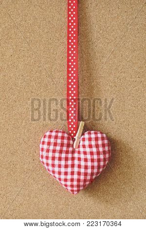 Red hearts shape pins garland over brown craft recycle cork board background. Free copy space. Valentine's day concept.