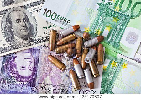 criminal money, few bullets on money dollars, pounds, euro, financial background