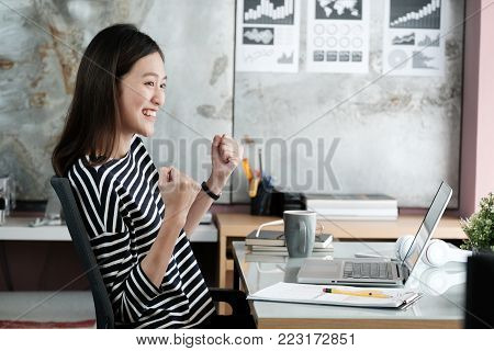 Young asian businesswoman arm up and smiling while sitting at her desk office, positive expression, sucess in business concept