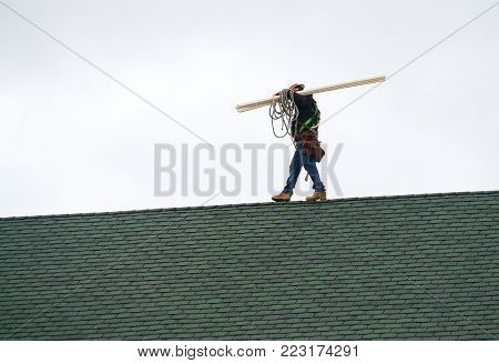 Manual roof repair worker walking on the roof carrying lumber wood