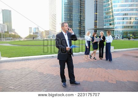Businessman speaking by smartphone outside, keeping blue document case with employees in background. Concept of boss conversation by mobile phone in La Defense Paris. Business partners talking about new project.