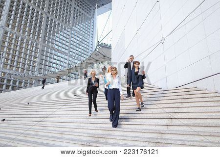 Foreign managers in official journey speaking on stairs with tablet and document cases. Concept of business trip and waiting for conference. Confident people talking in suits and white shirts.