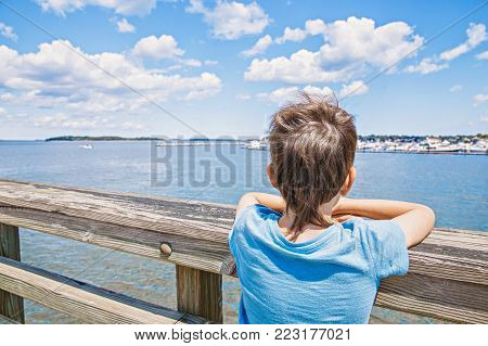 boy on the pier looks at the sea. child waiting on the dock by the sea. Back view. copy space for your text