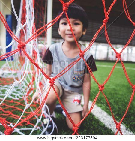 Little boy is sitting in Soccer goal net focus on the net