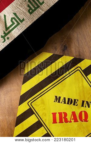 The national flag of Iraq on a wooden background with sigr made in Iraq
