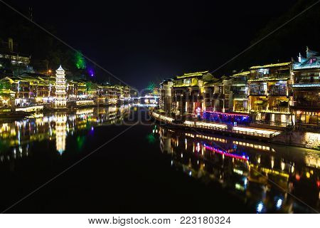 Night view of Fenghuang Ancient town, Hunan province, China. This ancient town was added to the UNESCO World Heritage Tentative List in the Cultural category.