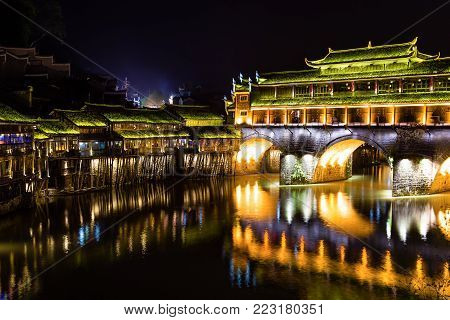 Hong Bridge at night in Fenghuang Ancient town, Hunan province, China. This ancient town was added to the UNESCO World Heritage Tentative List in the Cultural category.