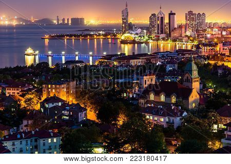 Qingdao Bay and the Lutheran church seen from the hill of Signal Park at night, Qingdao, China