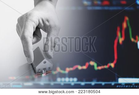 Hand holding house, with raising graph background. Real estate business and investment in real estate concept