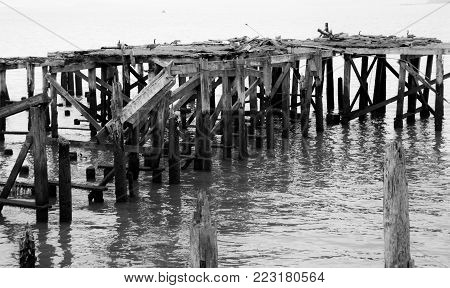 Dilapidated pier on an ocean inlet falling apart