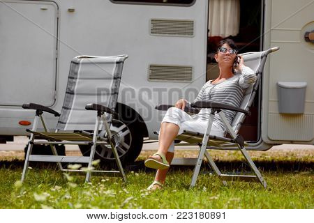 Woman talking on smart phone outdoors in a campsite for holidaymakers. Caravan car Vacation. Family vacation travel, holiday trip in motorhome RV. Connection information communication technology.