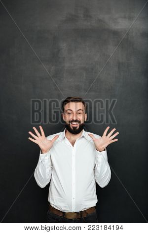 Image of male office worker gesturing on camera with hands up being cheerful over dark gray background
