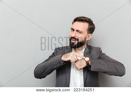 Horizontal image of bearded man pointing at his wrist watch posing isolated over gray background