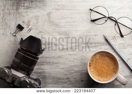 Mirror less camera, cup of hot coffee with foam, and glasses on the wooden shabby table. Morning planning concept, top view, copy space