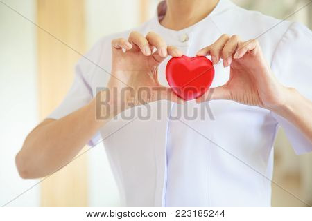 Red heart held by smiling female nurse's both hands, representing giving effort high quality service mind to patient. Professional, Specialist in white uniform concept