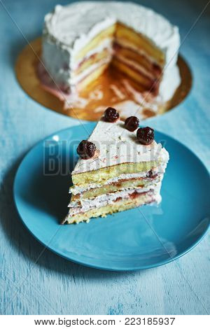 layered biscuit with curd cream and cherry. cake covered with curd cream and garnished with cherry on the blue plate on wooden background